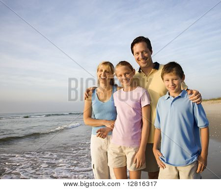 Portrait of Caucasian family of four posing on beach looking at viewer smiling.