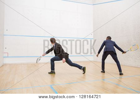 Business meeting of two businessmen playing squash. Warming up of two handsome men before real match in squash. ** Note: Soft Focus at 100%, best at smaller sizes