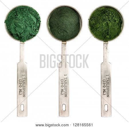 Nutrient-rich organic blue green algae, chlorella and spirulina powder - isolated measuring metal tablespoons, top view