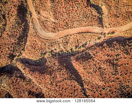 aerial view of a desert with a 4wd road and coarse vegetation near Moab, Utah - sunrise scenery with long shadows