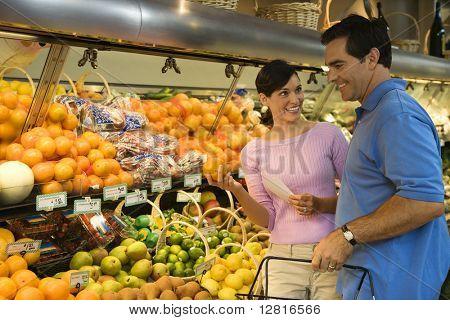 Pareja mid-adult caucásico compras fruta mirando sonreímos.