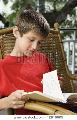 Caucasian pre-teen boy reading book.