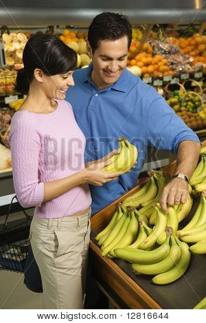 Caucasian mid-adult couple grocery shopping for bananas.