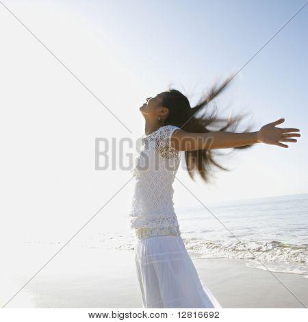 Junge asiatische Frauen am Strand warfen ihre Arme wieder hinter ihr.