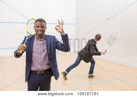 Happy businessman expressing positivity and showing okay sign during squash match while his colleague playing on squash court. ** Note: Visible grain at 100%, best at smaller sizes