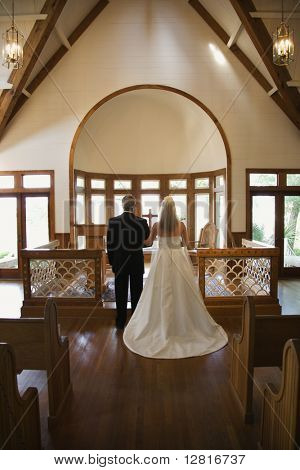 Portrait of bride and groom at alter of a church.