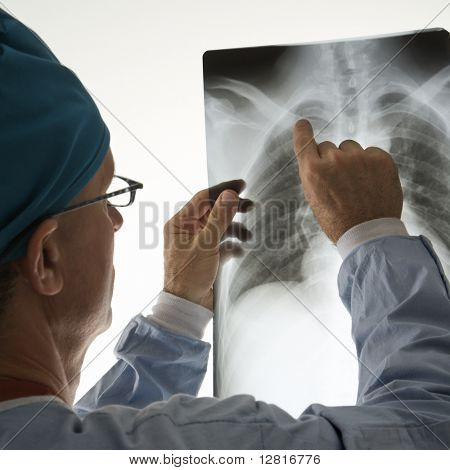 Mid-adult Caucasian male doctor pointing at a bone on a x-ray.