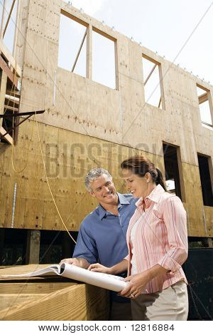 Caucasian mid-adult male and female looking at blueprints in construction phase of house.