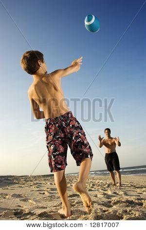 Muchacho preadolescente caucásico lanzando fútbol hombre mid-adult.