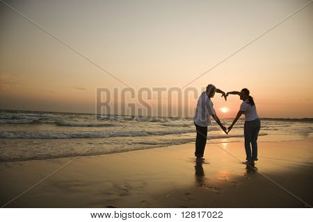 Mid-adult couple making heart shape with arms on beach at sunset.