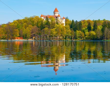 Chateau Konopiste with typical rounded tower reflecting in the water, Benesov, Czech Republic
