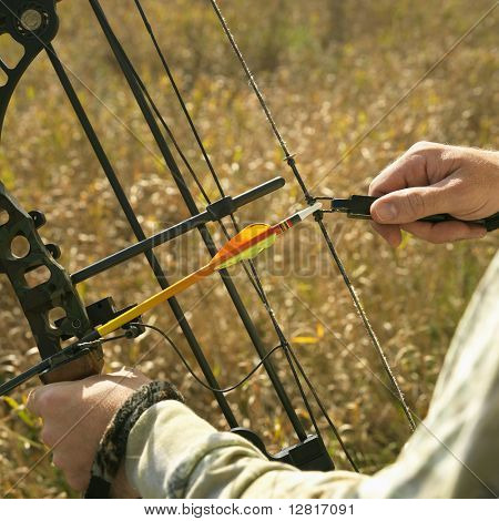 Manos de arco cazador con arco compuesto en campo.
