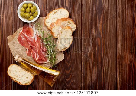 Prosciutto with rosemary and olive oil on wooden table. Top view with copy space
