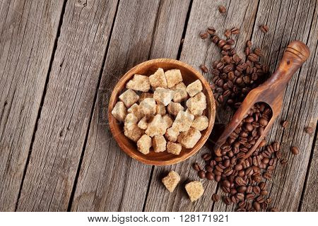 Coffee beans and brown sugar on wooden table. Top view with copy space