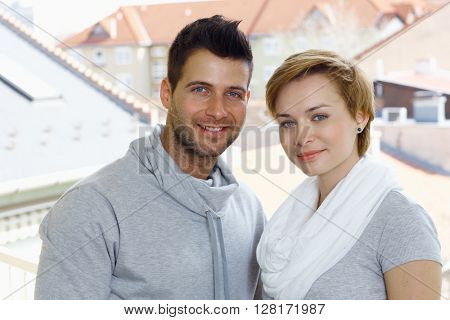 Closeup portrait of beautiful young couple smiling happy, looking at camera.