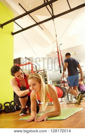 Young woman training with coach in fitness club.