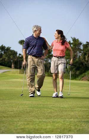 Lüneburg Mid Mann und Frau zu Fuß am Golfplatz, miteinander zu reden.