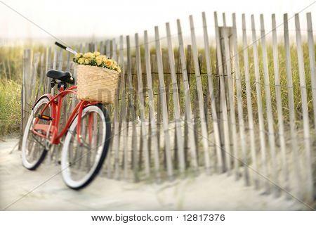 Rote Vintage Fahrrad mit Korb und Blumen gelehnt Holzzaun am Strand.