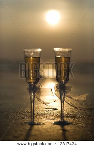 Pair of flute glasses filled with champagne with bows on stems on beach at sunset.