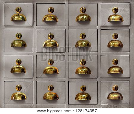 Rows of little drawers with golden handles in an old furniture module