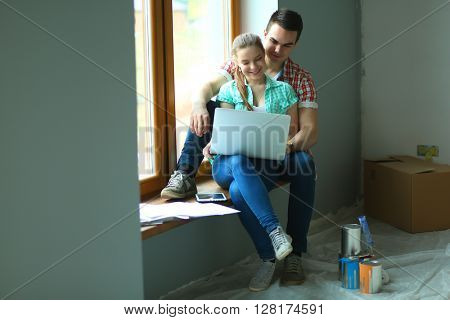 Portrait of young couple moving in new home sitting with laptop