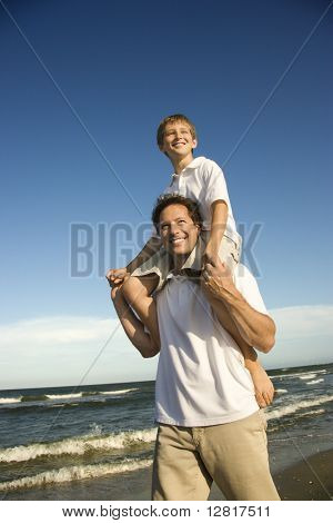 Caucasian father with pre-teen boy on shoulders on beach.