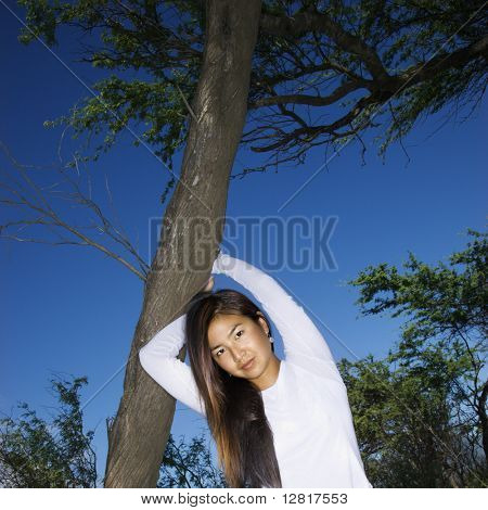 Young adult Asian female holding a tree and looking at viewer.