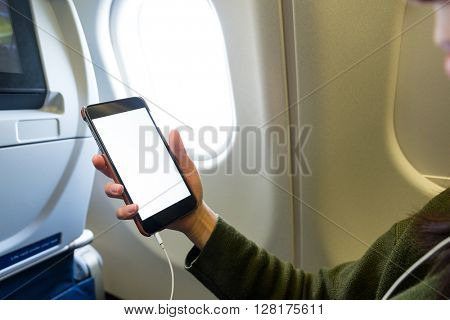 Woman using cellphone inside airplane