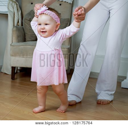 young mother teaching her baby walking at home