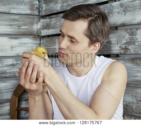 young handsome farmer with a duckling in his hands against wooden wall
