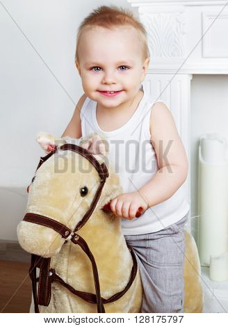 happy boy   at home with a toy horse