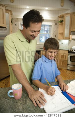 Caucasian mid-adult father helping pre-teen son with homework in kitchen.