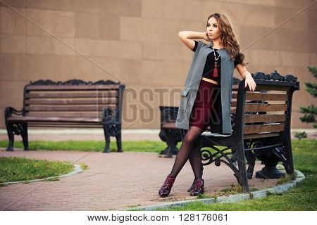 Happy young woman with long curly hairs walking on city street. Female fashion model in grey coat