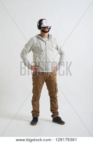 A young man in casual white hoody and khaki pants is smiling and watching something in virtual reality glasses with headphones on his head