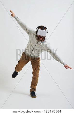 The picture in 3d reality glasses seems so real to the young man that he is trying to balance on one leg