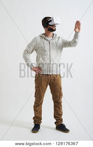 A young Caucasian man in casual clothes is watching something in virtual reality glasses with his headphones on, and trying to touch something with his hand