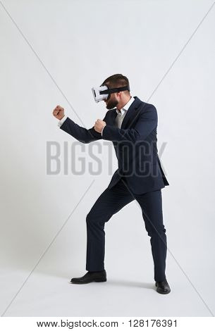Businessman in a formal wear and virtual reality glasses is standing in fighting pose