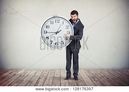 A young bearded man in business suit is holding a big round clock in his hands and emotionally pointing at it as if emphasizing on the time on the clock