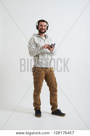 A young Caucasian bearded man in casual clothes with headphones on his head is smiling and holding a phone in his hands
