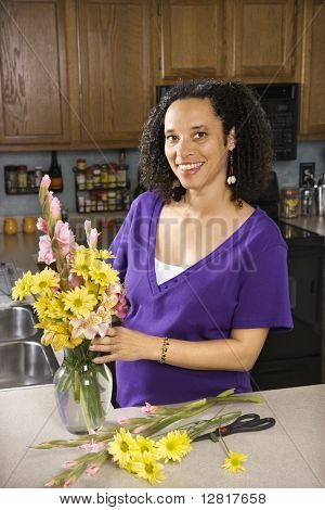 Portrait of young pregnant mother arranging flowers and looking at viewer.