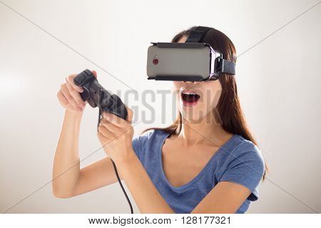 Woman playing video game wearing virtual reality headset
