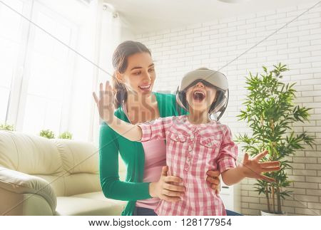 Happy family! Mother and her child daughter play game in virtual reality glasses.
