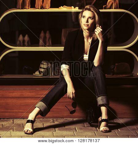 Young fashion woman sitting on the mall window. Female fashion model on night city street