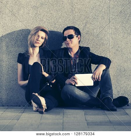 Young fashion couple with tablet computer sitting at the wall. Male and female fashion model. Man and woman outdoor