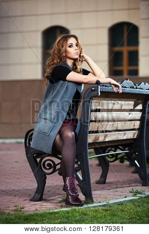 Sad young fashion woman with long curly hairs sitting on bench. Female fashion model in grey coat outdoor