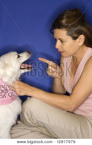 Caucasian prime adult female reprimanding fluffy white dog.