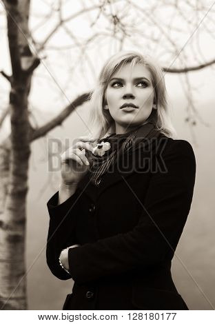 Young fashion woman walking in autumn forest. Female blond fashion model in black classic coat outdoor