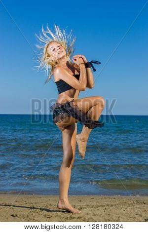 Portrait of beautiful young lady enjoying dancing on the beach