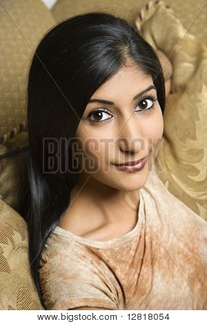 Close up portrait of Asian/Indian young woman sitting on couch.