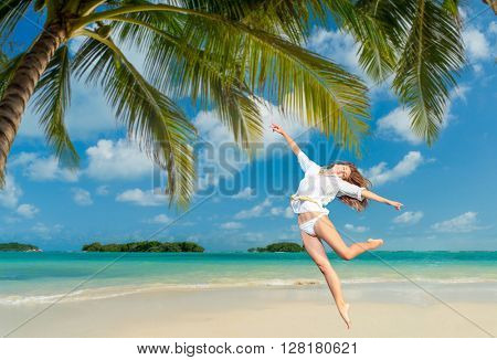 Woman jumping on the tropical beach